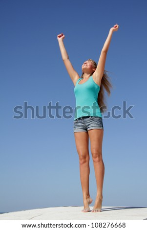 outdoor portrait of young happy woman isolated over blue sky