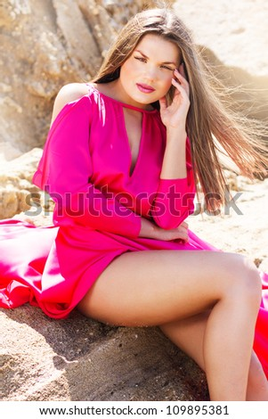 outdoor portrait of young sexy woman in long red dress