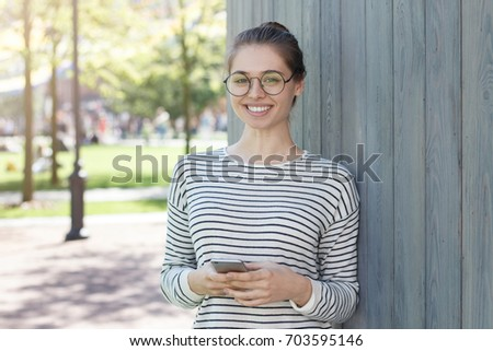 Outdoor portrait of young smiling European female standing against gray wooden wall wearing casual clothes and holding cellphone in hands, looking straight at camera while waiting for reply from web.