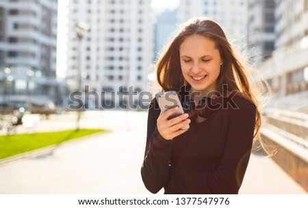 Outdoor portrait of young teenager brunette girl with long hair. girl on city in black dress looking on the smart phone walking in the street in a sunny day