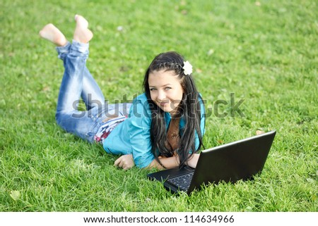 Outdoor portrait of young woman lying down using a laptop