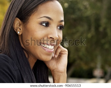 Outdoor portrait photo of attractive young woman with friendly smile