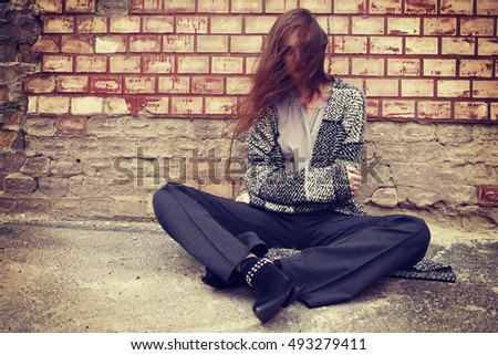 Outdoor portrait, street style fashion. Sad girl sits leaning on a brick wall. Frustrations, resentment and separation #493279411