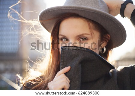 Outdoor portrait. Young stylish pretty woman with hat in hand posing in the big city streets.  #624089300