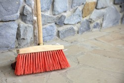 Outdoor red broom for house work on concrete wall background. sweeping the sidewalk