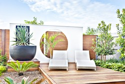 Outdoor relaxing area with the wooden decoration and trees from the garden including big and black vase, the pot includes a green leaf plant which also covered the area with walls at daytime