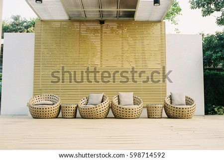 Outdoor relaxing space with trees around and rattan furniture inside