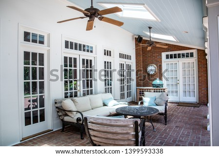 Outdoor Residential Back Patio Porch with Couches and Chairsand a Table #1399593338