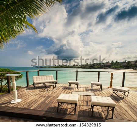 Outdoor restaurant at the beach. Cafe on the beach, ocean and sky. Table setting at tropical beach restaurant. Dominican Republic, Seychelles, Caribbean, Bahamas. Relaxing on remote Paradise beach.