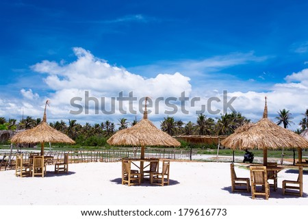 Outdoor restaurant at the beach. Cafe on the beach, ocean and sky. Table setting at tropical beach restaurant. lounge chairs for relaxing and sunbathing
