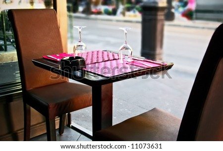 Outdoor restaurant in Paris, France, Europe. A table set for two person with an ashtray.