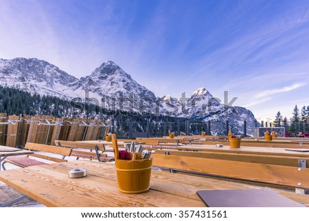 Outdoor restaurant in the mountains\ Image with the terrace of a restaurant, surrounded by the Alps mountains, with the rustic wooden tables ready to receive the guests.