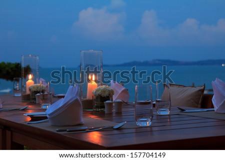 Outdoor restaurant table dinner setting on the beach at dusk