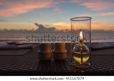 Outdoor restaurant table on the beach , wood weave table , candle light , blurred sunset background . #451167079