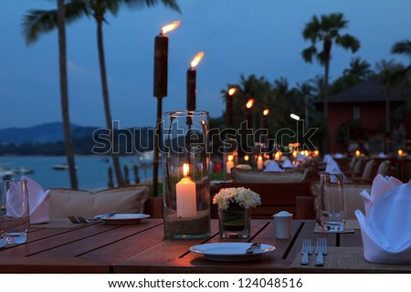 Outdoor restaurant tables, dinner setting on the beach at evening