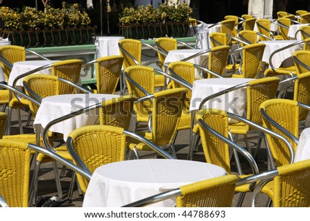 Outdoor restaurant tables with yellow chairs. Cafe patio in Venice, Italy.