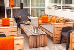 Outdoor restaurant terrace with wooden furniture in scandinavian style. Eco-friendly authentic design.