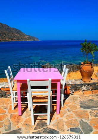 Outdoor restaurant - traditional greek tavern with pink table and white chairs overlooking Mediterranean sea (Crete, Greece ). Vertical image - stock photo