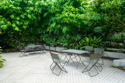 Outdoor seats in a courtyard surrounded by green leafy plants.