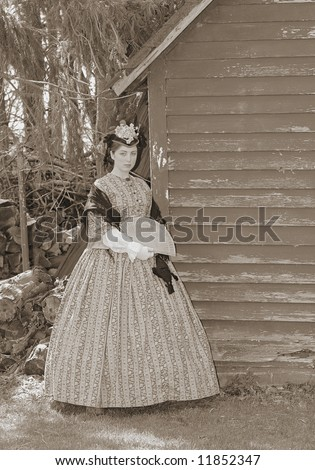 outdoor sepia portrait of an attractive young girl in a Civil War era 1860s dress