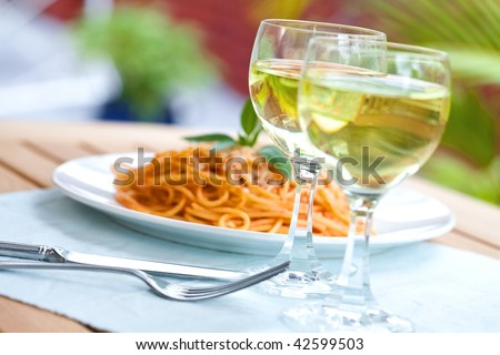 Outdoor setting, a plate of spaghetti with two glasses of wine