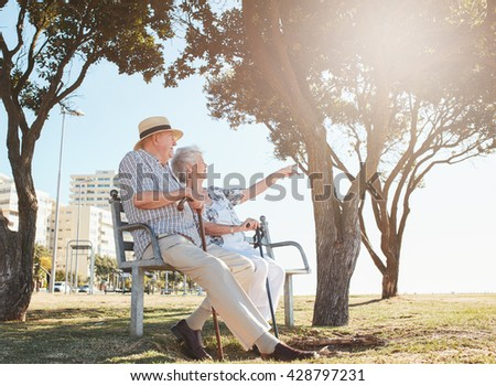 Shutterstock Outdoor shot of a senior couple sitting on a park bench with woman showing something interesting to her  husband. Retired couple taking a break and relaxing on a bench.
