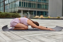 Outdoor shot of active slim young woman practices yoga leans forward stretches arms dressed in activewear poses on knees at fitness mat poses outdoors in city center against urban background