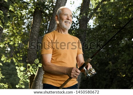 Outdoor shot of attractive unshaven senior Caucasian male holding spinning rod cast in river waters, smiling with anticipation, waiting for fish to be hooked, flare sun and green trees in background #1450580672