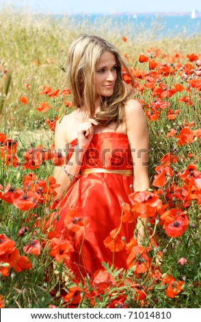 Outdoor shot of beautiful woman in red dress near the sea