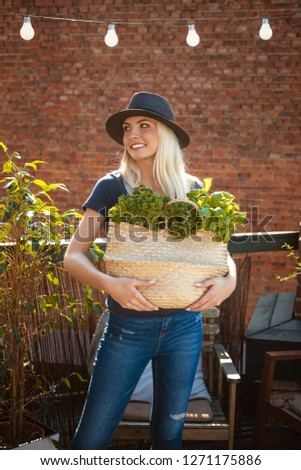 Outdoor shot of beautiful young woman holding basket with kale, basil and green vegetables. Slow life concept.