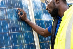 Outdoor shot of black African engineer inspect electrical solar panel wearing hardhat , protective eyeglass and safety equipment with smile on his face. Alternative energy and industrial job concept.
