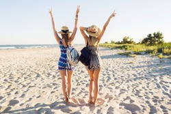 Outdoor shot of cheerful young female friends are back with their hands raised together on a beach at sunset . Two attractive women enjoying a holiday on the sea shore.