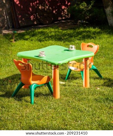 Outdoor shot of children plastic chair and table on grass at yard