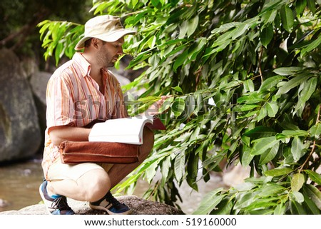 Outdoor shot of ecologist wearing hat and striped shirt sitting in front of green plant while examining its leaves for diseases holding manual or guide on his laps, looking for required information