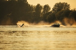 Outdoor shot of man wakeboarding on lake at sunset. Water skiing on lake behind a boat.