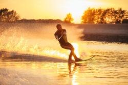 Outdoor shot of man water skiing at sunset . Man wakeboarding on a lake.