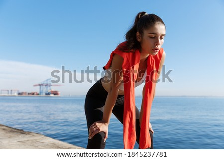 Outdoor shot of tired fitness woman panting and taking a breath after jogging, standing on a pier with sea behind her Photo stock ©