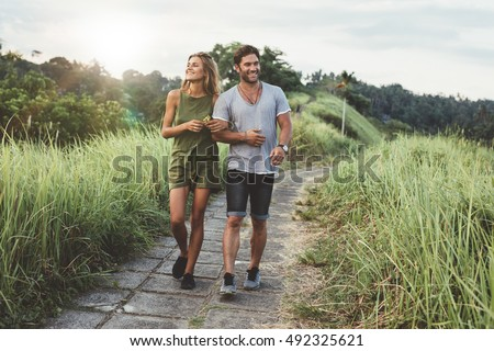 Outdoor shot of young couple in love walking on pathway through grass field. Man and woman walking along tall grass field. stock photo
