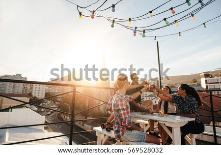 Outdoor shot of young people toasting drinks at a rooftop party. Young friends hanging out with drinks. #569528032