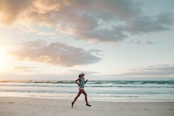 Outdoor shot of young sports woman running along the sea shore in morning. Fitness female doing running exercise on the beach.