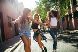 Outdoor shot of young women having fun on city street. Female friends enjoying a day around the city.