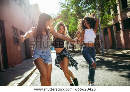 Outdoor shot of young women having fun on city street. Female friends enjoying a day around the city. Stockfoto ©