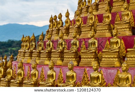 Outdoor Shrine of Many Sitting Gold Buddhas on Circular Platform with View of Nature Mountains in Distance (Huay Xai, Bokeo, Laos). #1208124370