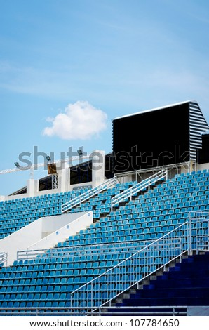 outdoor sport arena with black digital score board over stadium with blue seat