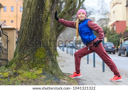 Outdoor sport exercises, sporty outfit ideas. Woman wearing warm sportswear training exercising outside during autumn, warming up before workout. #1041321322