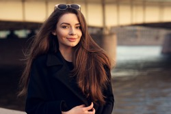 Outdoor spring or autumn portrait of young beautiful pretty woman with long hair posing in city at sunset