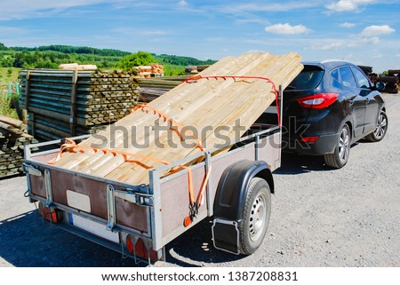 Outdoor stacking the logs on utility trailer for transport at sawmill in europe with background green forest ,blue sky and clouds. industrial wood yard with stacks of new wood poles.  #1387208831