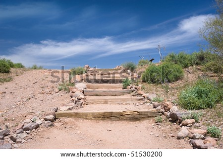 Outdoor stairs in the desert leading to a bright blue sky