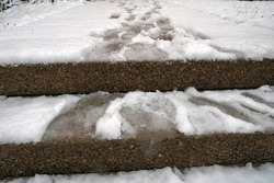Outdoor steps covered with snow and  shoe imprints and dog paws in it. The snow has not been cleared away. Slippery ground is risky and dangerous because of potential accident. Photo at low angle.