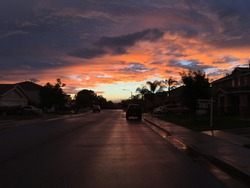 Outdoor street photo of mid or after sunset. Pink and dark clouds mixed with beautiful blue sky. Silhouetted neighborhood on street with reflected pink skies on asphalt and sidewalk.